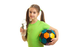 La niña linda con el balón de fútbol en manos bebe el agua en botella Fotografía de archivo libre de regalías