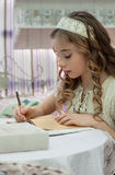 La niña linda con el pelo largo en un vestido del vintage escribe en una n Fotografía de archivo