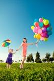 La niña linda con la madre coloreó los globos y el umbrel del arco iris Imagen de archivo libre de regalías