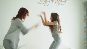 La niña linda con su madre cariñosa se divierte que baila el estilo moderno junta que salta y que da el alto cinco en cama almacen de metraje de vídeo