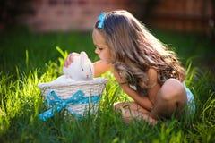 La niña linda con un conejo de conejito tiene una pascua en la hierba verde