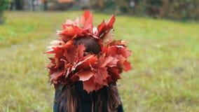 La niña linda de la visión trasera en una corona de la guirnalda de las hojas de arce del otoño camina en la cámara lenta del par metrajes