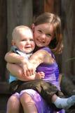 La niña linda detiene a un bebé y sonríe Imagen de archivo