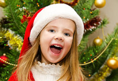 La niña linda en el sombrero de santa con el presente tiene una Navidad Foto de archivo