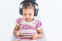 La niña linda en un vestido multicolor, escucha la música con los auriculares y utiliza un smartphone en un fondo blanco imagenes de archivo
