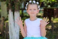 La niña linda en un vestido y una guirnalda azules y blancos aumenta sus manos, él dijo - hola Foto de archivo