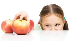 La niña está alcanzando la manzana imagen de archivo
