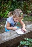 La niña linda está dibujando en el papel en el jardín imagenes de archivo