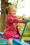 La niña linda está haciendo pivotar en el balancín Imagen de archivo libre de regalías