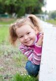 La niña linda está jugando escondite Foto de archivo