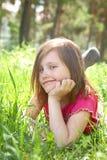 La niña linda está mintiendo en prado verde Foto de archivo libre de regalías
