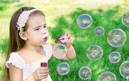 La niña linda está soplando burbujas de un jabón Fotografía de archivo libre de regalías