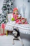La niña linda feliz se vistió en los pijamas rayados que se sentaban en sitio adornado de Año Nuevo en casa Fotos de archivo libres de regalías