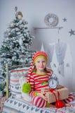 La niña linda feliz se vistió en los pijamas rayados que se sentaban en sitio adornado de Año Nuevo en casa Imágenes de archivo libres de regalías