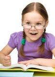 La niña linda golpea un libro con el puño Imagen de archivo libre de regalías