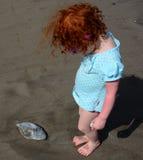 La niña linda ha encontrado pescados viejos en la playa imagen de archivo