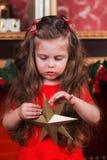 La niña linda hace que la Navidad la decoración protagoniza en un árbol de navidad imágenes de archivo libres de regalías