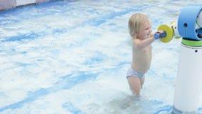 La niña linda juega con el canon del agua en piscina almacen de metraje de vídeo