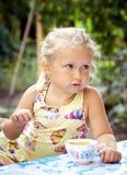 La niña linda lame una cuchara con un helado delicioso en el A.C. imagenes de archivo