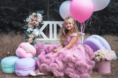 La niña linda lleva a cabo el francés Macaron Concepto de la confitería fotografía de archivo libre de regalías
