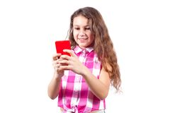 La niña linda mira en smartphone y la sonrisa imagen de archivo