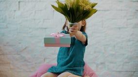 La niña linda muestra flores y un regalo