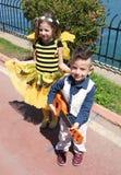 La niña linda no identificada con manosea el traje de la abeja y su presentación del hermano Imagenes de archivo