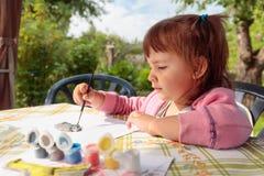 La niña linda pinta las figuras animales imagen de archivo