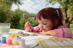 La niña linda pinta las figuras animales imagen de archivo libre de regalías