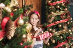 La niña linda que lleva la venda roja abre el regalo cerca del árbol de navidad fotos de archivo