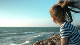 La niña linda que se sienta en la playa mira la cámara lenta de las ondas almacen de metraje de vídeo