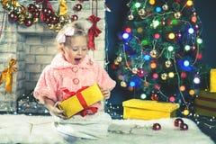 La niña linda recibe un árbol de navidad de adornamiento cercano del regalo Imagen de archivo