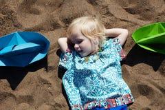 La niña linda se cayó dormido en la arena Imágenes de archivo libres de regalías