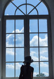 La niña linda se coloca cerca de una ventana y mira el cielo con las nubes Imagen de archivo