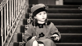 La niña linda se vistió en capa del retro-estilo dentro de la casa vieja Foto de archivo libre de regalías
