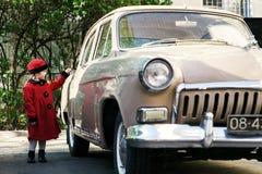 La niña linda se vistió en la capa retra que presentaba cerca del coche del oldtimer Imágenes de archivo libres de regalías