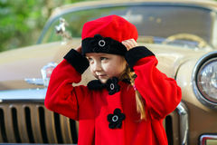 La niña linda se vistió en la capa retra que presentaba cerca del coche del oldtimer Imagenes de archivo