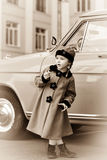 La niña linda se vistió en la capa retra que presentaba cerca del coche del oldtimer Imagen de archivo libre de regalías