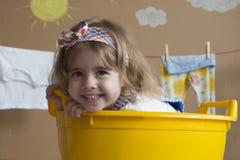 La niña linda sonríe y se sienta en un baño amarillo Foto de archivo