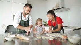La niña linda y sus padres hermosos están cocinando Se divierten mucho junto y sonriendo en cocina en casa metrajes