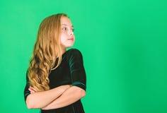 La niña lleva el vestido oscuro del terciopelo parece elegante y adorable Poco elegancia de la falta Pelo rizado largo del niño l imágenes de archivo libres de regalías