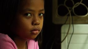 La niña malhumorada, triste o enojada solamente mira fijamente la cámara Emoción del niño metrajes