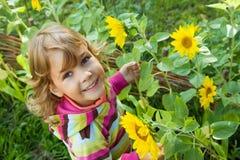 La niña mantiene el girasol disponible jardín Fotografía de archivo libre de regalías