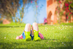La niña maravillosa juega con en la hierba verde de la primavera Imagenes de archivo