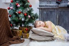 La niña miente en las almohadas en un vestido amarillo, la Navidad foto de archivo