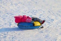 La niña miente en snowtube abajo de la colina Imagen de archivo
