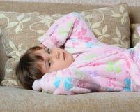 La niña miente en un sofá Imagenes de archivo