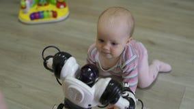 La niña mira cuidadosamente el robot y las danzas del juguete con él Tecnologías robóticas modernas almacen de metraje de vídeo
