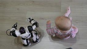 La niña mira cuidadosamente el robot y las danzas del juguete con él Tecnologías robóticas modernas almacen de video