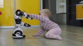 La niña mira cuidadosamente el robot y las danzas del juguete con él Tecnologías robóticas modernas metrajes